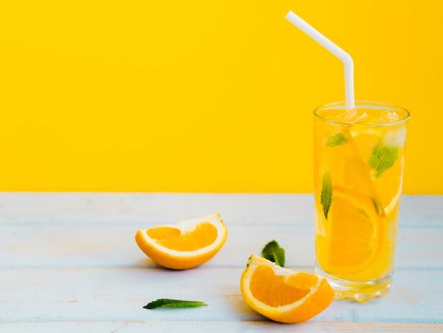 Exuberante vaso húmedo de zumo de naranja con menta