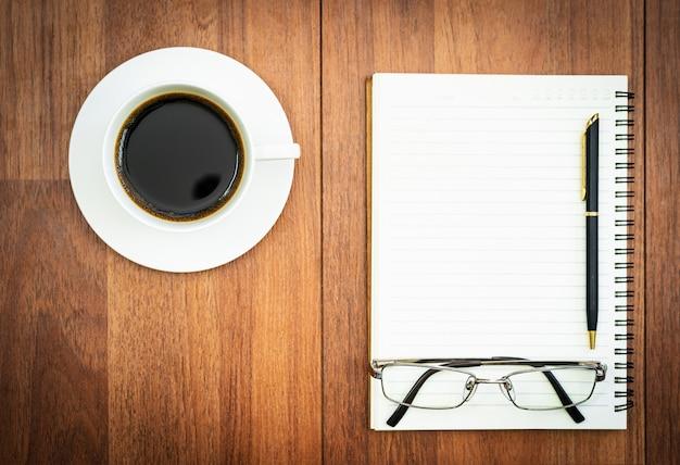 Eyeglasse y bloc de notas con taza de café en la cubierta de madera