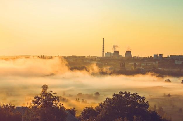 Fábrica y campo con niebla