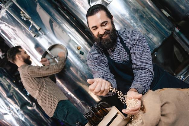 Fábrica de cerveza artesanal tradicional hombre vierte granos.