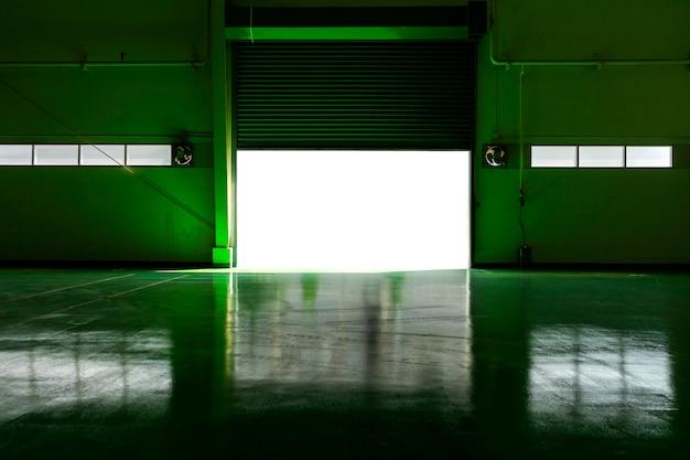 Fábrica de metal con puerta y zona verde con luz del sol.