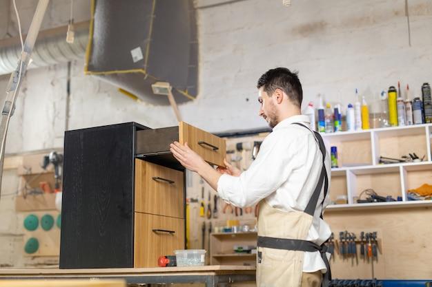 Fábrica de muebles, pequeñas empresas y concepto de personas - joven que trabaja en la producción de muebles
