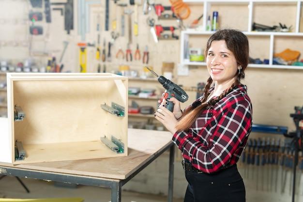 Fábrica de muebles, pequeñas empresas y concepto de trabajadora - mujer con un taladro en la fábrica.