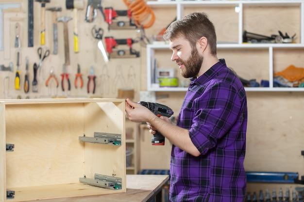 Fabricación, pequeñas empresas y concepto de trabajador - hombre que trabaja en la fábrica de muebles.