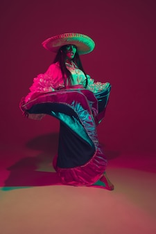 Fabulosa bailarina del cinco de mayo en la pared púrpura del estudio en luz de neón