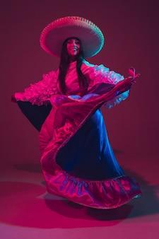 Fabulosa bailarina del cinco de mayo en pared púrpura en luz de neón.