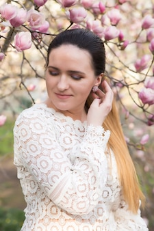 Fabulosa mujer morena con maquillaje nude, vistiendo blusa de encaje, posando cerca de las flores de magnolia en flor