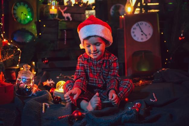 Un fabuloso ambiente navideño. niño feliz en pijama hermoso y gorro de papá noel en adornos navideños. luz de color. foto para una postal.