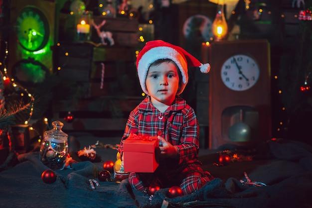 Un fabuloso ambiente navideño. un niño sostiene una caja con un regalo en sus manos en las decoraciones de año nuevo. luz de color. foto para una postal.