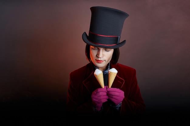 Fabuloso hombre de circo con un sombrero y un traje rojo posando en el humo en una oscuridad