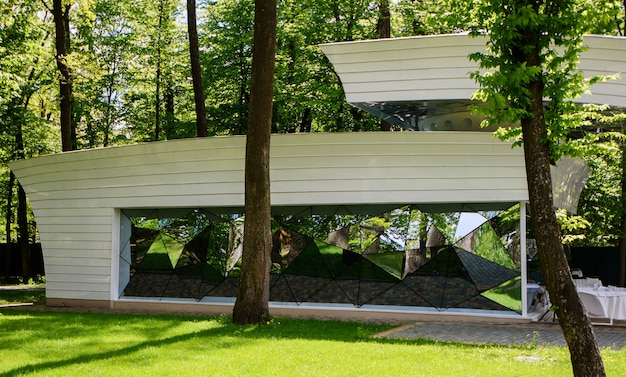 Fachada de la casa con ventanas espejadas en el parque.