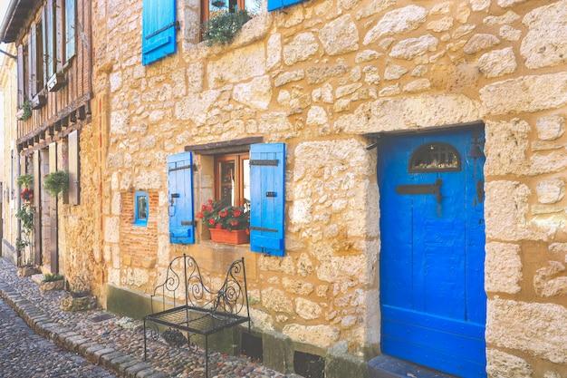 Fachada de casas de piedra con puertas de madera y ventanas azules en la ciudad de bergerac, francia