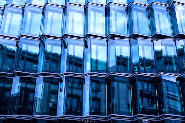 Fachada de cristal moderna de un edificio de oficinas, reflejo del cielo en las ventanas.
