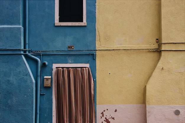 Fachada de un edificio con fondo sucio azul y amarillo