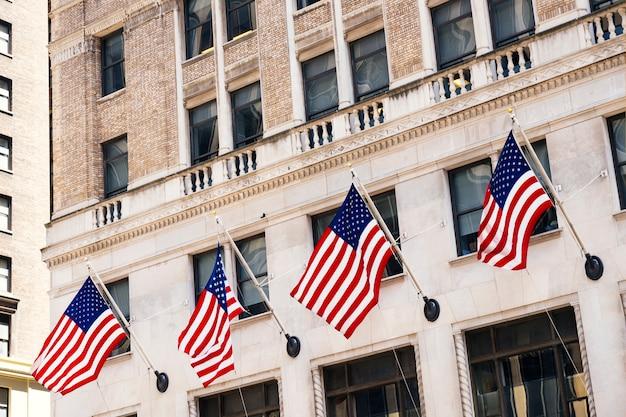 Fachada de edificio de piedra decorada con banderas americanas.
