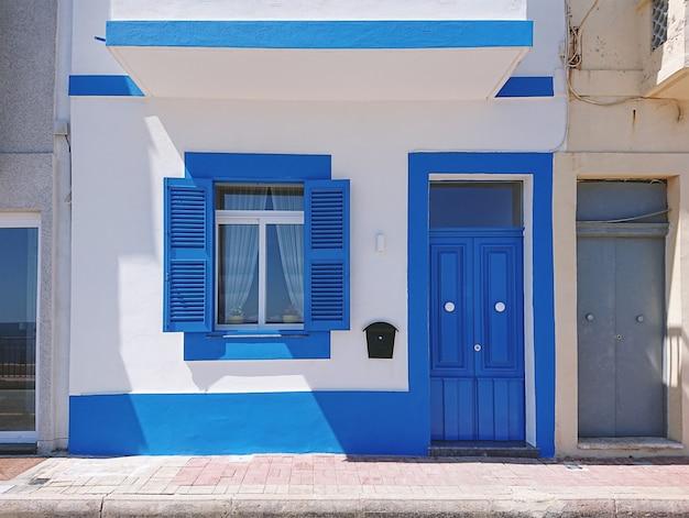 Fachada frontal de edificio residencial con puerta azul y ventana.
