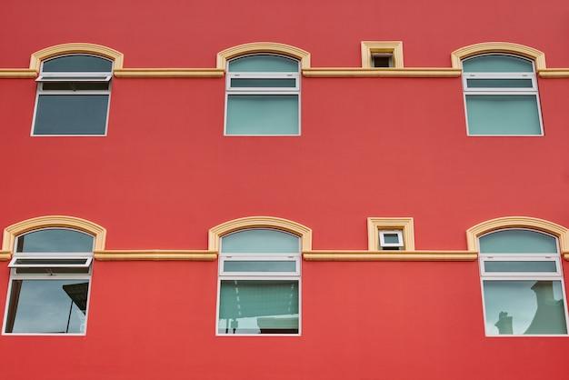 Fachada del hotel de color salmón con ventanas y balcones simétricos