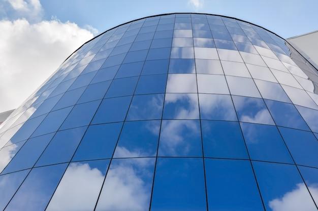 Fachada de vidrio de un moderno edificio de oficinas contra un cielo azul con nubes