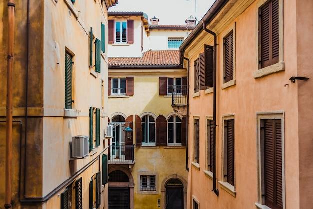 Fachadas descoloridas y antiguas de casas en el casco antiguo de la ciudad de verona, edificios tradicionales italianos.