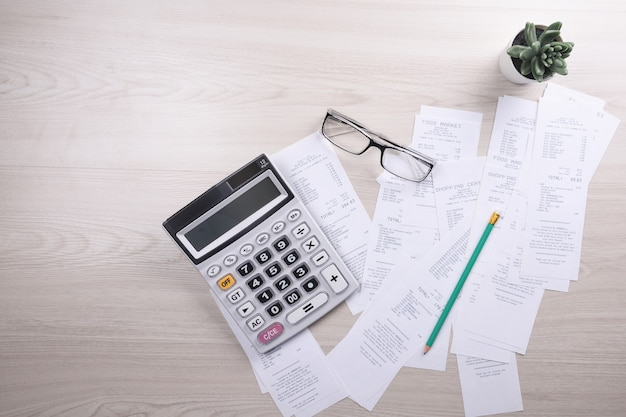 Factura de servicios públicos y calculadora con lápiz. análisis de datos financieros.