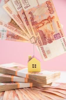 Facturas inmobiliarias con escaleras hechas de dinero y casa