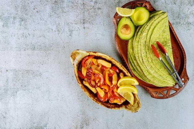 Fajita en bandeja para hornear con tortillas de limón y espinacas en la mesa blanca