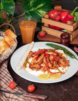 Fajita de pollo, filete de pollo frito con pimiento en lavash con rebanadas de pan en un plato blanco