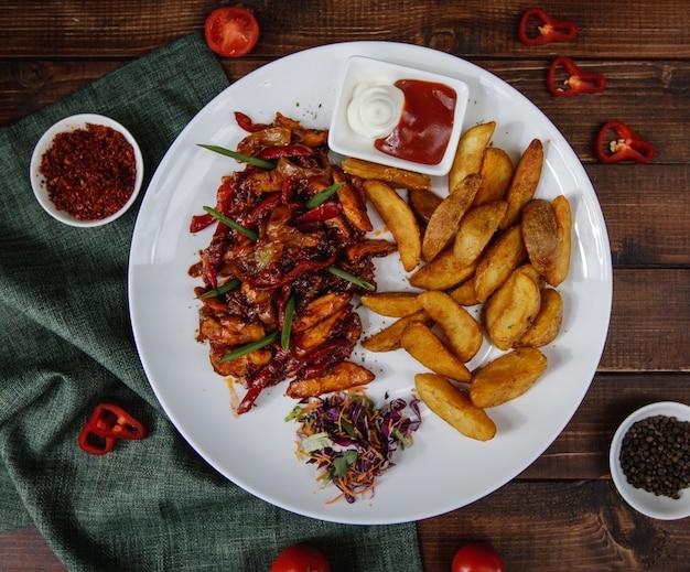 Fajitas de pollo con papas asadas servidas con salsas y ensalada