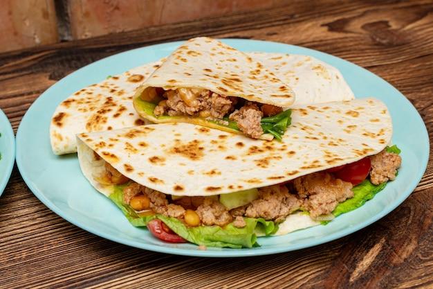 Fajitos con verduras de carne picada en una tortilla de maíz sobre una placa azul fondo de madera oscura. concepto de comida tradicional de comida rápida