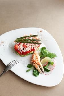 Falange de cangrejo con ensalada, limón y espárragos