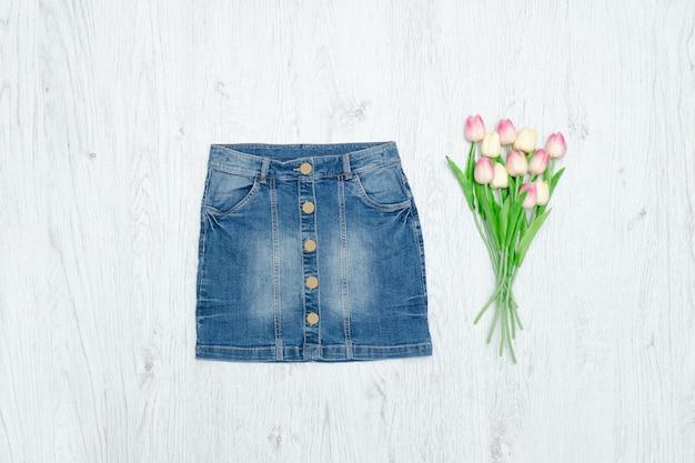 Falda vaquera azul y ramo de tulipanes. concepto de moda