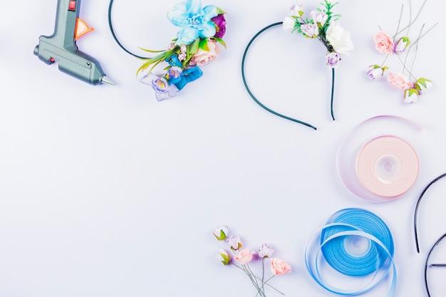 Falsas flores artificiales y cintas para hacer la diadema sobre un fondo blanco.