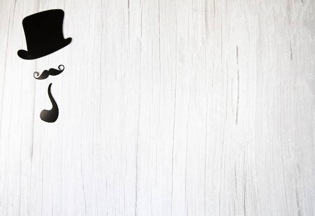 Falso bigote, lazo de corbata y sombrero sobre un fondo blanco de madera. día internacional del hombre y el concepto del día del padre endecha plana, vista superior, espacio de copia