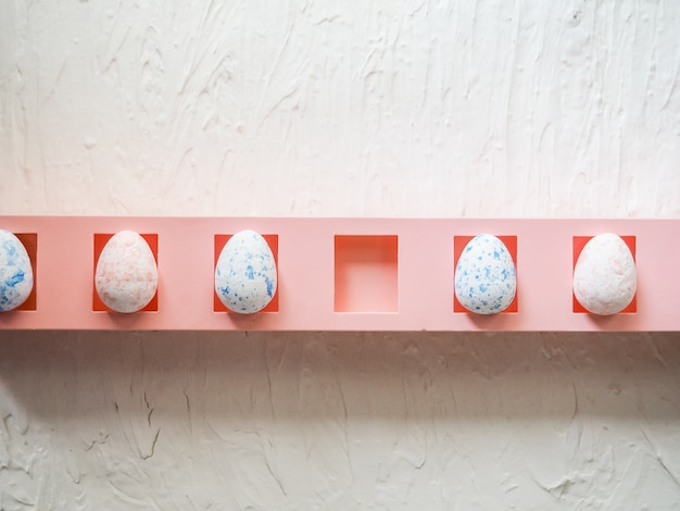 Faltan huevos artificiales en una caja, recoge una celda, concepto de pascua. huevos de espuma blanca sobre fondo azul. vista plana, vista superior. concepto de pascua