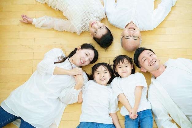 Familia de 3 generaciones tendida en el suelo de la habitación.