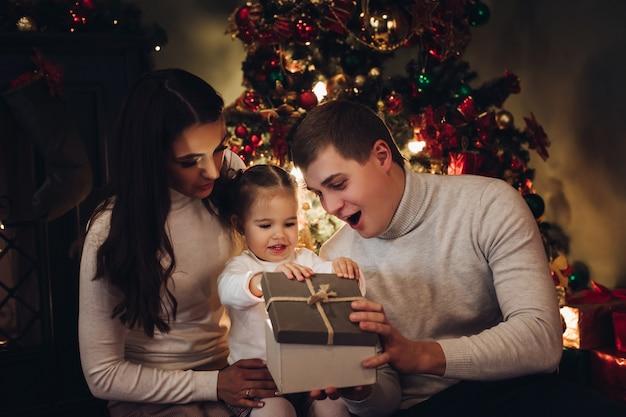 Familia abriendo regalo de navidad juntos. habitación decorada para navidad.