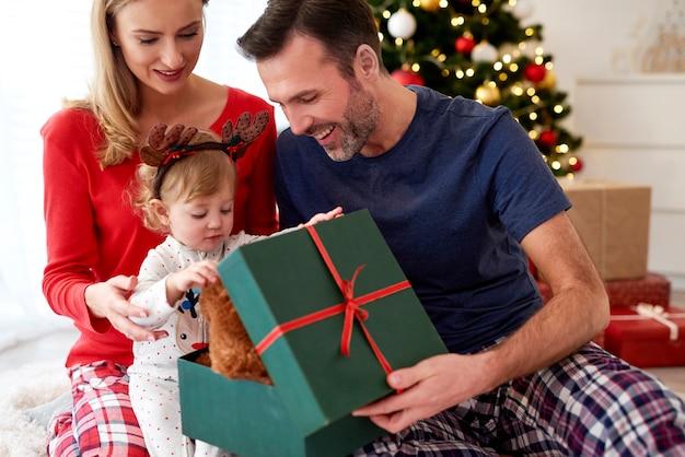 Familia abriendo regalos de navidad en la cama
