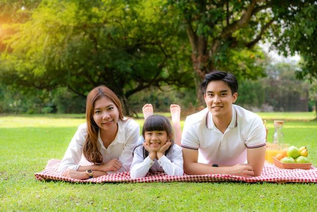 Familia adolescente asiática feliz día de fiesta picnic en el parque con el padre, la madre y la hija acostada en la estera y sonríen felices de pasar tiempo de vacaciones juntos en el jardín verde con frutas y alimentos.