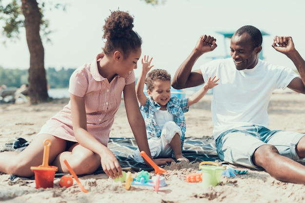 Familia afro de madre, padre e hijo en la playa de río.