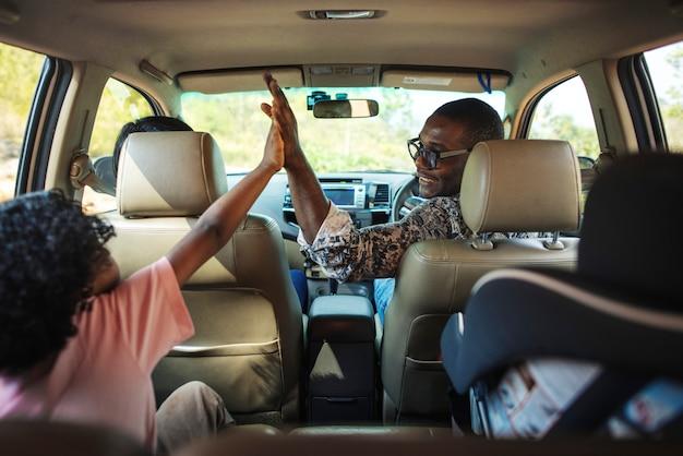 Familia alegre en un coche en un viaje por carretera