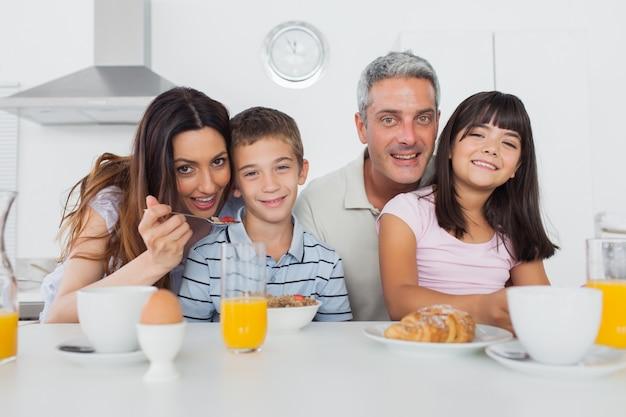 Familia alegre desayunando en la cocina juntos