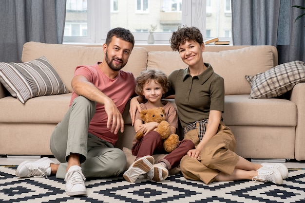 Familia alegre de joven pareja cariñosa y su adorable hijo pequeño en ropa casual sentados en el suelo sobre una alfombra blanca y negra junto al sofá