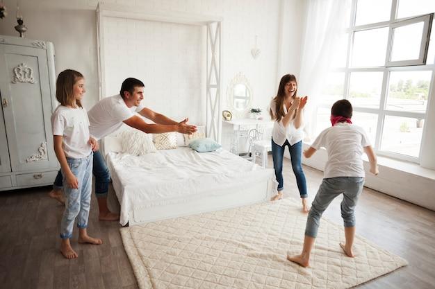 Familia alegre jugando con los ojos vendados y riendo en casa.
