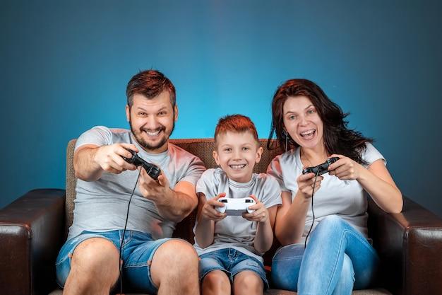Una familia alegre, padre, madre e hijo juegan en la consola, los videojuegos, reaccionan emocionalmente sentados en el sofá. día libre, entretenimiento, ocio, pasar tiempo juntos.