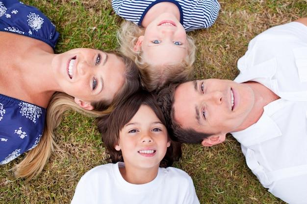 Familia alegre que miente en círculo en la hierba