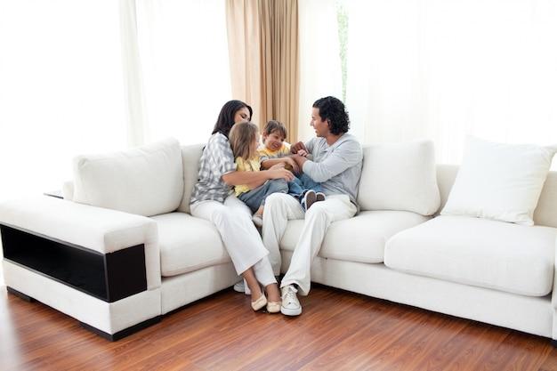 Familia animada divirtiéndose sentada en el sofá