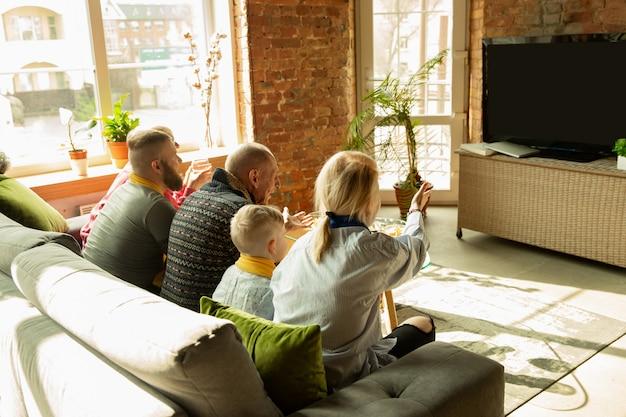 Familia animando y viendo televisión en casa en la sala de estar