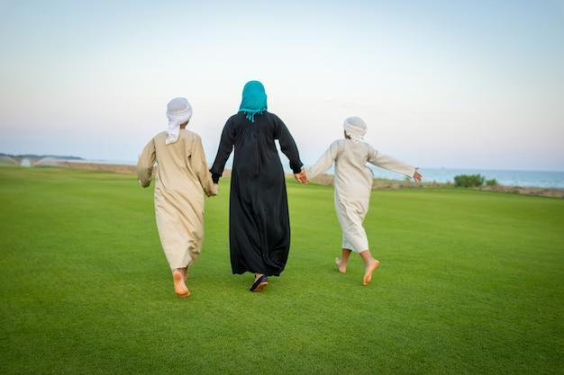 Familia árabe en prado verde en la naturaleza