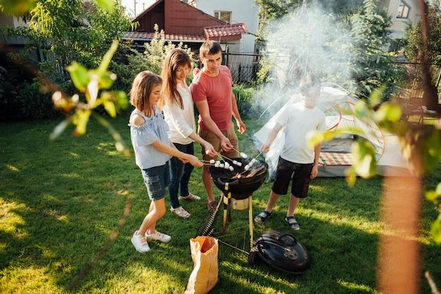 Familia asar malvaviscos en parrilla de barbacoa en el parque