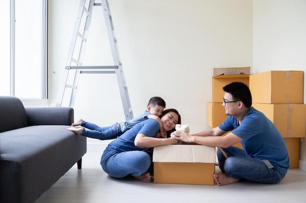Familia asiática desempacando cajas de cartón en su nuevo hogar, reubicándose para un nuevo concepto de propiedad inmobiliaria